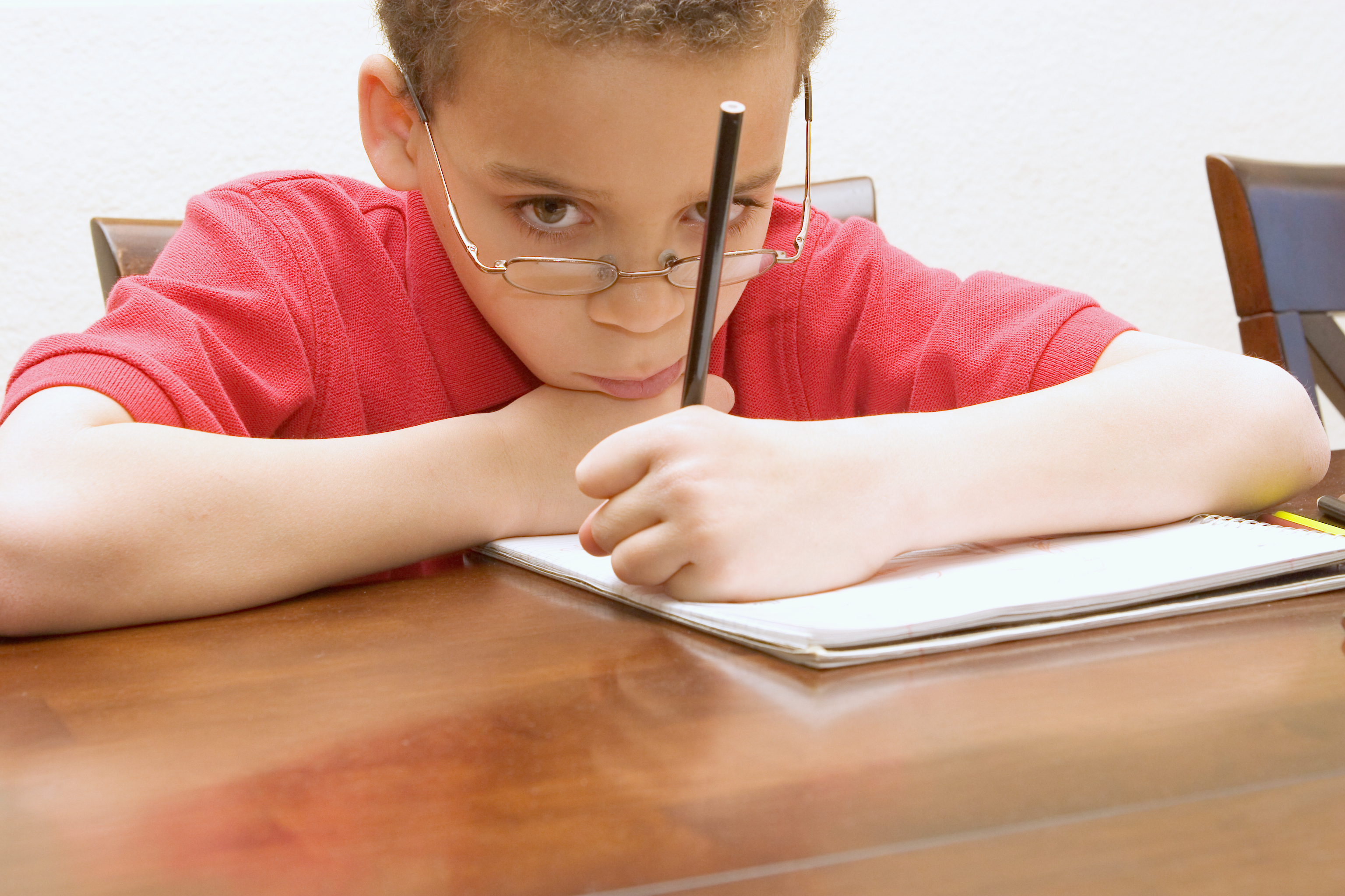 Left handed young boy wearing glasses reluctant to do homework not paying attention, staring into space.